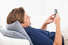 Άτομο που χρησιμοποιεί το έξυπνο τηλέφωνο στον καναπέ Στοκ φωτογραφία με δικαίωμα ελεύθερης χρήσης