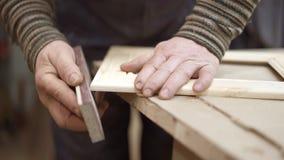 Άτομο που χρησιμοποιεί το γυαλόχαρτο στο ξύλινο πλαίσιο που βρίσκεται στον πίνακα στο εργαστήριο απόθεμα βίντεο