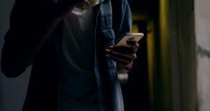 Άτομο που χρησιμοποιεί το κινητό τηλέφωνο ενώ έχοντας τα τρόφιμα 4k απόθεμα βίντεο