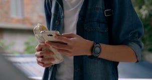 Άτομο που χρησιμοποιεί το κινητό τηλέφωνο ενώ έχοντας τα τρόφιμα 4k φιλμ μικρού μήκους