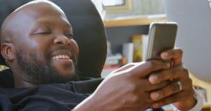 Άτομο που χρησιμοποιεί το κινητό τηλέφωνο σε ένα άνετο σπίτι 4k φιλμ μικρού μήκους