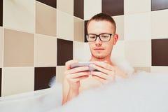 Άτομο που χρησιμοποιεί το κινητό τηλέφωνο στο λουτρό Στοκ εικόνες με δικαίωμα ελεύθερης χρήσης