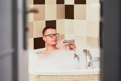 Άτομο που χρησιμοποιεί το κινητό τηλέφωνο στο λουτρό Στοκ φωτογραφία με δικαίωμα ελεύθερης χρήσης