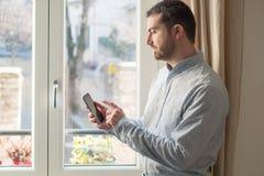 Άτομο που χρησιμοποιεί το κινητό τηλέφωνό του στο σπίτι Στοκ εικόνα με δικαίωμα ελεύθερης χρήσης