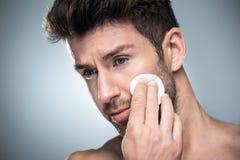 Άτομο που χρησιμοποιεί το μαξιλάρι βαμβακιού στο πρόσωπο στοκ εικόνα με δικαίωμα ελεύθερης χρήσης