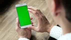 Άτομο που χρησιμοποιεί το τηλέφωνο με την πράσινη επίδειξη οθόνης στο γραφείο απόθεμα βίντεο