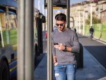 Άτομο που χρησιμοποιεί το τηλέφωνο στη στάση λεωφορείου Στοκ εικόνες με δικαίωμα ελεύθερης χρήσης