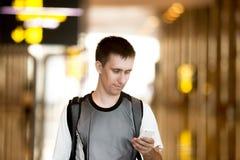 Άτομο που χρησιμοποιεί το τηλέφωνο κυττάρων στον αερολιμένα Στοκ φωτογραφία με δικαίωμα ελεύθερης χρήσης