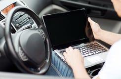 Άτομο που χρησιμοποιεί το φορητό προσωπικό υπολογιστή στο αυτοκίνητο Στοκ Εικόνες