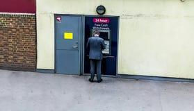 Άτομο που χρησιμοποιεί το ATM για να αποσύρει τα μετρητά στοκ φωτογραφία