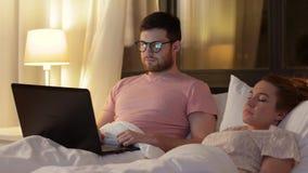 Άτομο που χρησιμοποιεί το lap-top ενώ η φίλη κοιμάται απόθεμα βίντεο