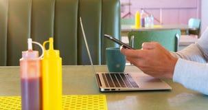 Άτομο που χρησιμοποιεί το lap-top και το κινητό τηλέφωνο ενώ έχοντας τον καφέ 4k απόθεμα βίντεο