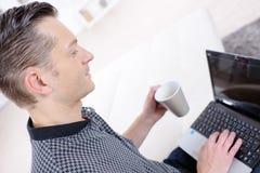 Άτομο που χρησιμοποιεί το lap-top πίνοντας τον καφέ Στοκ Φωτογραφίες