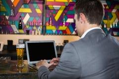 Άτομο που χρησιμοποιεί το lap-top στο φραγμό στοκ εικόνες με δικαίωμα ελεύθερης χρήσης