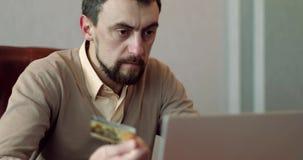 Άτομο που χρησιμοποιεί το lap-top του και μια πιστωτική κάρτα στο γραφείο του απόθεμα βίντεο