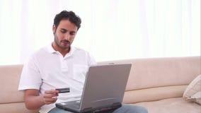 Άτομο που χρησιμοποιεί το lap-top του και μια πιστωτική κάρτα φιλμ μικρού μήκους