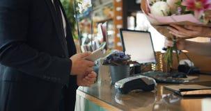 Άτομο που χρησιμοποιεί το smartphone για να κάνει την πληρωμή στο κατάστημα ανθοκόμων που παίρνει έπειτα την ανθοδέσμη
