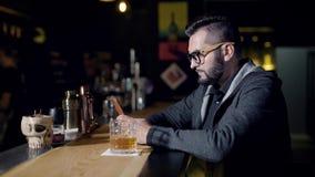 Άτομο που χρησιμοποιεί το smartphone κοντά στο ποτήρι του ποτού στο μετρητή φραγμών απόθεμα βίντεο