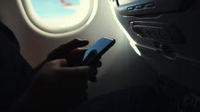 Άτομο που χρησιμοποιεί το smartphone σε ένα αεροπλάνο, φιλμ μικρού μήκους