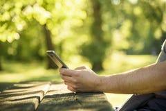 Άτομο που χρησιμοποιεί το smartphone στη φύση Στοκ φωτογραφία με δικαίωμα ελεύθερης χρήσης