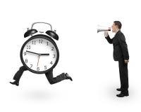 Άτομο που χρησιμοποιεί megaphone να φωνάξει το τρέχοντας ρολόι με τα ανθρώπινα πόδια Στοκ Φωτογραφίες