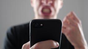 Άτομο που χρησιμοποιεί Smartphone Εξαγριωμένο φωνάζοντας άτομο με το smartphone διαθέσιμο φιλμ μικρού μήκους
