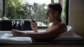 Άτομο που χρησιμοποιεί Smartphone στην μπανιέρα στο λουτρό Το άτομο έλαβε ένα κακό μήνυμα και παρουσιάζει θυμό Βία κινδύνου απόθεμα βίντεο