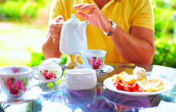 Άτομο που χύνει το αγγλικό τσάι στο φλυτζάνι, στο θερινό κήπο Στοκ Φωτογραφία