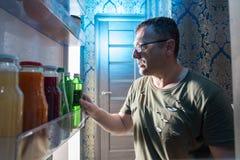 Άτομο που ψάχνει για ένα μπουκάλι του ποτού σε ένα ψυγείο στοκ εικόνες