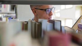 Άτομο που ψάχνει το βιβλίο στα ράφια στη βιβλιοθήκη στο κολλέγιο απόθεμα βίντεο