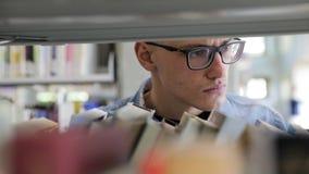 Άτομο που ψάχνει το βιβλίο στα ράφια στη βιβλιοθήκη στο κολλέγιο φιλμ μικρού μήκους