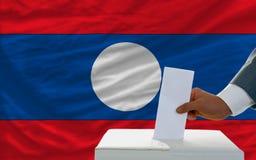 Άτομο που ψηφίζει για τις εκλογές στο Λάος μπροστά από τη σημαία Στοκ φωτογραφίες με δικαίωμα ελεύθερης χρήσης