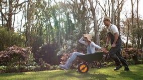 Άτομο που ωθεί τη φίλη του wheelbarrow φιλμ μικρού μήκους