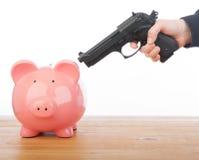 Άτομο που δείχνει ένα πυροβόλο όπλο σε μια piggy τράπεζα Στοκ Εικόνες