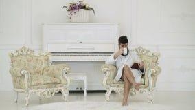 Άτομο σε έναν καφέ κατανάλωσης μπουρνουζιών και ανάγνωση μιας συνεδρίασης βιβλίων σε μια πολυθρόνα ενάντια σε ένα άσπρο πιάνο Άτο απόθεμα βίντεο