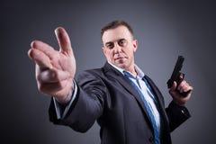 Άτομο σε ένα επιχειρησιακό κοστούμι με ένα πυροβόλο όπλο στοκ φωτογραφίες με δικαίωμα ελεύθερης χρήσης