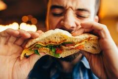 Άτομο σε ένα εστιατόριο που τρώει ένα χάμπουργκερ Στοκ εικόνες με δικαίωμα ελεύθερης χρήσης