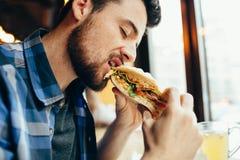 Άτομο σε ένα εστιατόριο που τρώει ένα χάμπουργκερ στοκ εικόνα