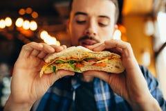 Άτομο σε ένα εστιατόριο που τρώει ένα χάμπουργκερ στοκ φωτογραφίες με δικαίωμα ελεύθερης χρήσης