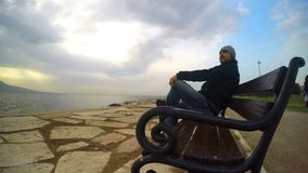 Άτομο σε ένα κάθισμα κοντά στη θάλασσα απόθεμα βίντεο