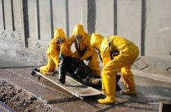 Άτομο σε ένα κίτρινο χημικό κοστούμι προστασίας Στοκ εικόνες με δικαίωμα ελεύθερης χρήσης