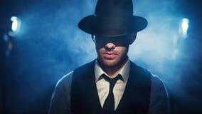 Άτομο σε ένα καπέλο σε ένα σκοτεινό υπόβαθρο Στοκ Εικόνα