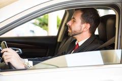 Άτομο σε ένα κοστούμι που οδηγεί ένα αυτοκίνητο Στοκ Εικόνες
