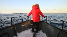 Άτομο σε ένα κόκκινο σακάκι στο τόξο του σκάφους φιλμ μικρού μήκους