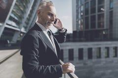 Άτομο σε ένα μαύρο κοστούμι που μιλά στο τηλέφωνο Στοκ Εικόνες