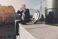 Άτομο σε ένα μαύρο κοστούμι που μιλά στο τηλέφωνο Στοκ φωτογραφία με δικαίωμα ελεύθερης χρήσης