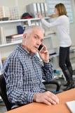 Άτομο σε κινητό κατά τη διάρκεια της εργασίας Στοκ Φωτογραφία