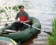 Άτομο σε μια βάρκα με τα κουπιά, νεαρός άνδρας που χαμογελά σε μια βάρκα στοκ εικόνα με δικαίωμα ελεύθερης χρήσης