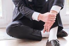 Άτομο σε μια συνεδρίαση κοστουμιών στο πάτωμα στοκ εικόνες