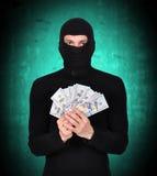 Άτομο σε δολάρια εκμετάλλευσης μασκών Στοκ φωτογραφία με δικαίωμα ελεύθερης χρήσης